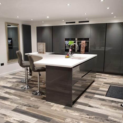 Kitchen island with tall housings behind, all finished in basalt grey gloss, with white corian worktop on the island