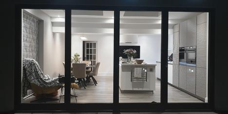 brightly lit kitchen and dining area viewed through bi-fold glass doors at night