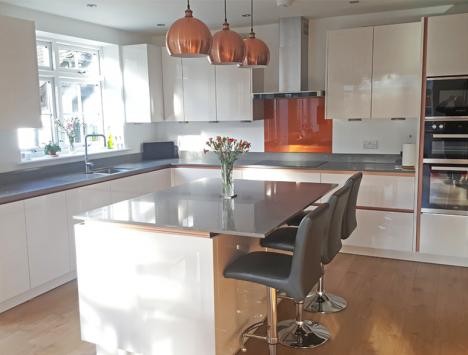 Magnolia high gloss handleless kitchen with copper handle trims and grey quartzstone worktop
