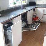 open kitchen units revealing integrated bins, dishwasher and carousel fitted under the sink run worktop