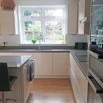 Looking towards the window in a kitchen with glossy magnolia units and grey quartz worktops