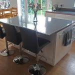 High gloss kitchen island with quartz worktop sized to create a breakfast bar for 3
