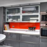 Grey gloss kitchen with orange splashbacks and Corian tops