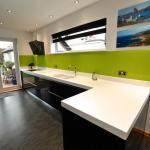 contemporary handleless fitted kitchen, Corian worktops, glass splashbacks