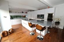 contemporary handleless white kitchen. Glass worktops. AEG appliances