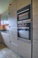 Fitted kitchen features a Kuppersbusch double oven